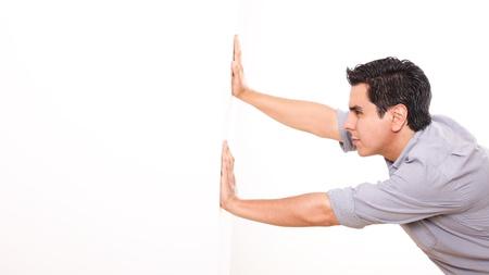 Hombre empujando una pared blanca sobre fondo blanco