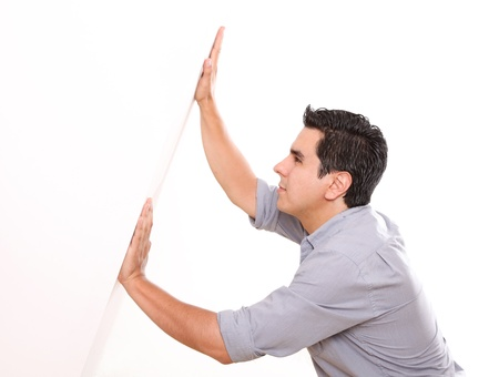something: Man holding a white wall over white background