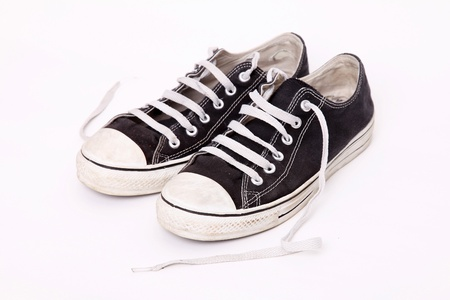 Pair of shoes worn with the laces loose over white background