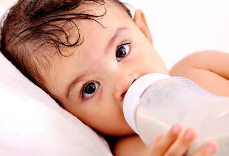 baby biberon: Baby bere latte della sua bottiglia. Sfondo bianco