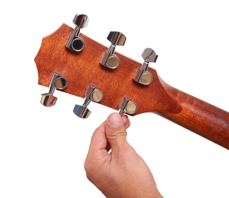 Person tuning a guitar from its  headstock over white background photo