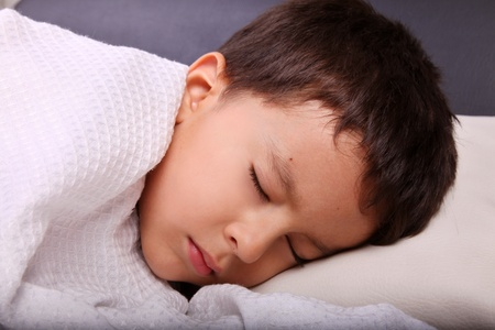 Child sleeping in bed with the blanket disposal indoors photo