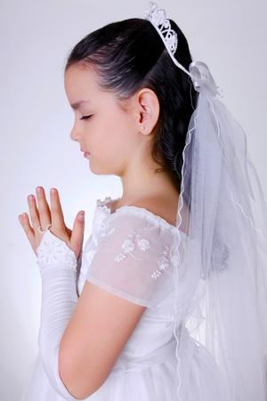 holy communion: Chica orando concentrado en su primera comuni�n  Foto de archivo