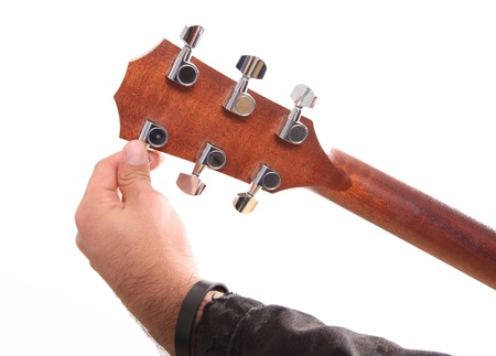 Tuning a guitar from its  headstock over white background  photo