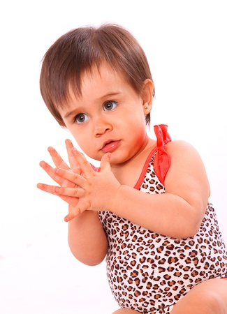 baby girl clapping with swimsuit isolated over white background photo