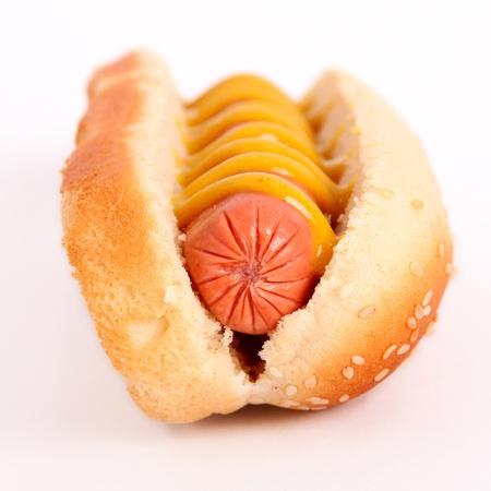 perro caliente: hot dog con chorizo, mostaza, salsa de tomate y pan sobre fondo blanco