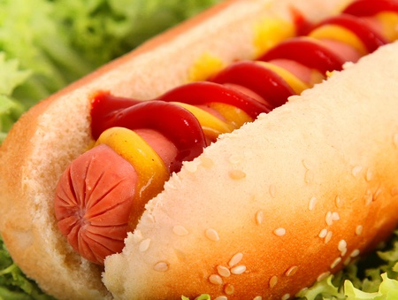 hot dog with sausage,bread,ketchup and mustard over lettuce background