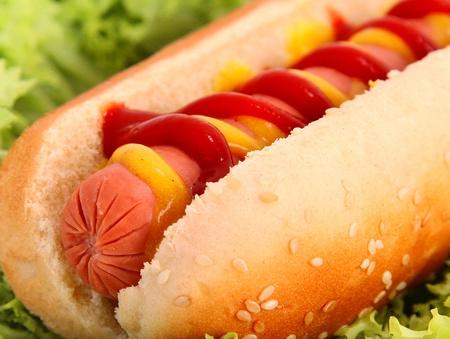 perro caliente: perro caliente con salchicha, pan, ketchup y mostaza sobre el fondo de lechuga