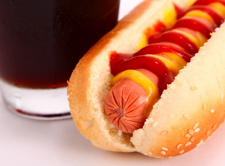 carbonated drink: black drink and hot dog over lettuce over white background Stock Photo