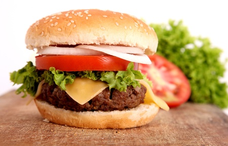 hamburger with bread,tomato,onion,lettuce,meat,cheese,ham over cutting board wooden photo