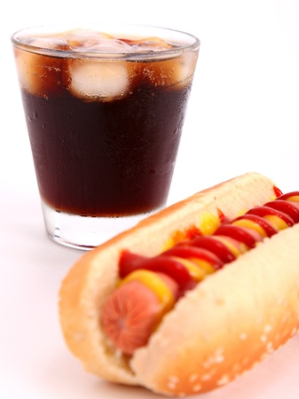 black drink and hot dog over lettuce over white background photo