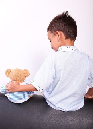 boy with a teddy bear sitting with his back photo