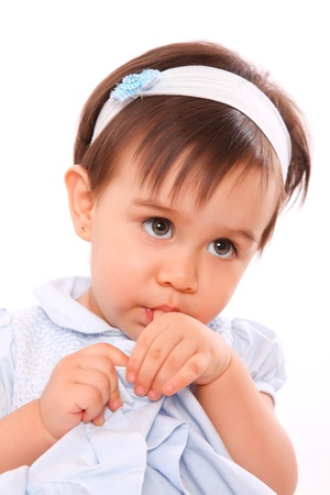 comforted: baby girl sucking her thumb with blue dress Stock Photo