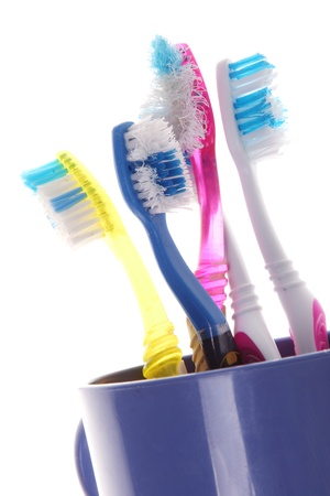 and worn out: old toothbrushes in a blue glass on white background