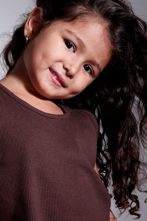 curly hair child: beautiful smiling girl with brown blouse close up Stock Photo
