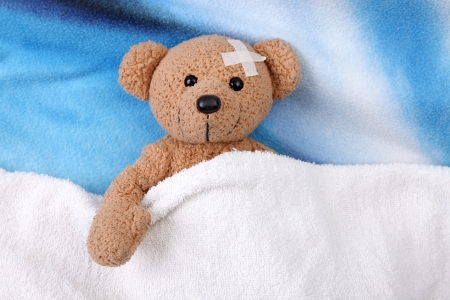 테디는 침대 위에 접착 붕대 아픈 곰입니다. 가까이 스톡 콘텐츠