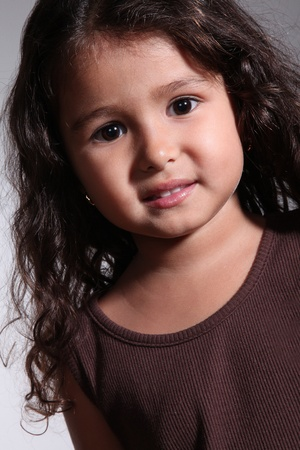beautiful child girl with curly hair and brown blouse. close up photo