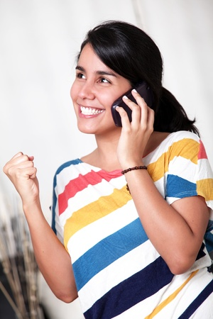 Young girl with positive attitude talking on mobile phone photo