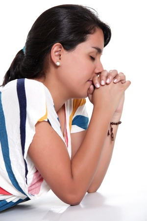 worship white: woman praying with eyes closed and hands together