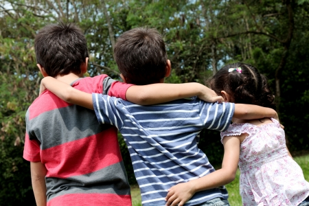 children of different ages embraced as a sign of brotherhood photo