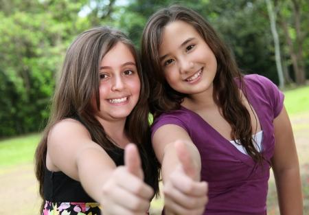 positivism: dos amigos levantando su dedo a la c�mara indica el positivismo