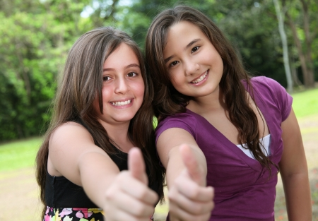 positivism: two friends raising his finger at the camera indicating positivism Stock Photo