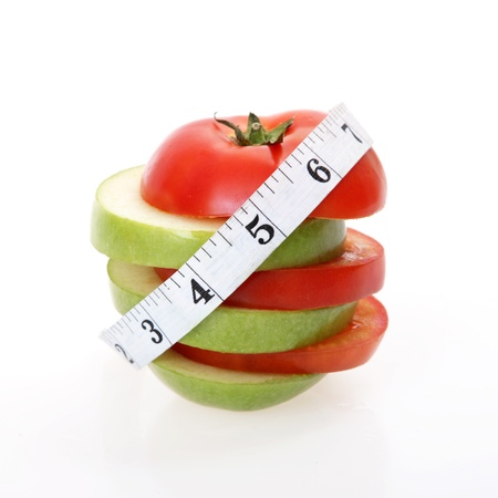 sliced tomatoes and apples forming a tower with a meter over white background Stock Photo - 15397056