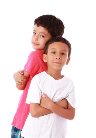 Two children standing back to back over white background photo