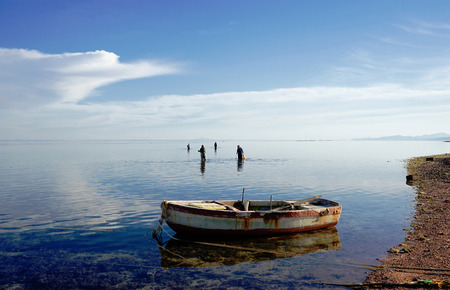 dahab: Red Sea in a calm weather. Bedouin women on the reef. Dahab. Egypt.