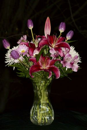 Bouquet of flowers in green vase on black background