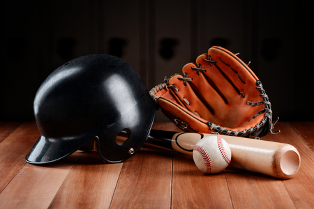 Baseball equipment and gear items on a wooden table. Catchers helmet, glove, bat and ball.