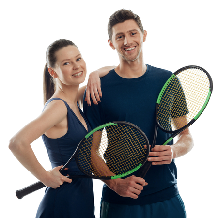 Couple of young tennis players on white. Woman leant on mans shoulder, both holding racquets and giving friendly smiles.