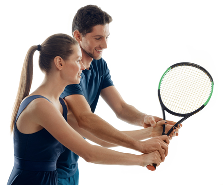 Male coach and female beginner on white. Skillful player showing how to hold a racquet right. Reklamní fotografie