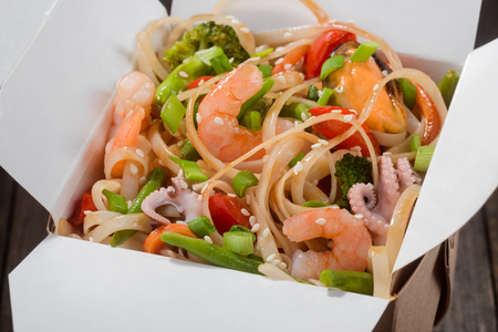 Delicious asian food in take-out box. Close up on noodles with fried vegetables and seafood then stirred soy sauce. Food delivery service.