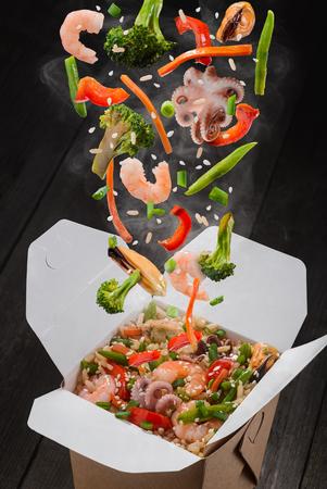 Arroz con verduras y marisco. Ingredientes como pulpos, mejillones, gambas, brócoli, pimiento, lechuga, espárragos, arroz y semillas de sésamo cayendo en caja para llevar.