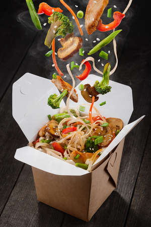 Chinese noodles with vegetables. Ingredients are falling into box: noodles, chicken meat, mushrooms, broccoli, pepper, lettuce, asparagus and sesame seeds. Presentative photo of food product. Imagens