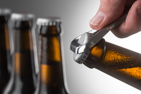 Opening cold bottle of beer using a metal opener. Three more unopened bottles over grey wall in unfocused background. Banco de Imagens