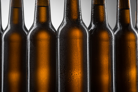 Close up of beer bottles on grey background. Row of dark brown bottles covered with condensate. Water drops on glass. Stock Photo