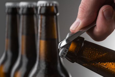 Male hand opening beer bottle using metal opener. Droplets on brown bottles of cold beer. Selective focus. Stock fotó