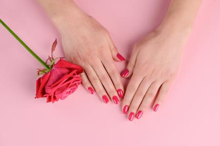 Hand met rode nagels. Kleur geïnspireerd op de tint van roze bloemen. Een eenvoudige en mooie stijl krijgen bij een manicuresalon.