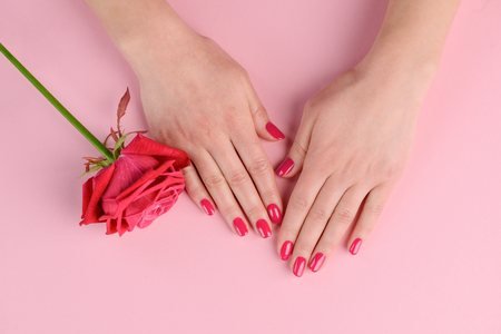 Hand with red nails. Color inspired by hue of rose flower. Getting simple and nice style at manicure salon.