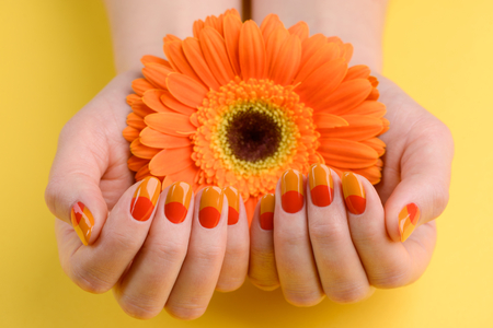 Gerbera in womans hands. Nails painted orange and red colors. Bright summer manicure art. Stock Photo
