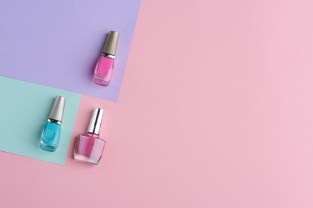Set of nail varnishes. Vivid blue, pink and dark pink. Manicure cosmetics background with copy space. Stock Photo