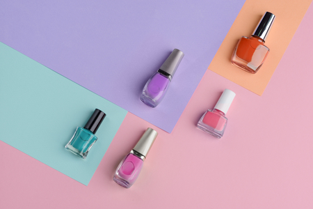 Trendy colors of nail polishes. Turquoise, violet, dark orange and shades of pink.