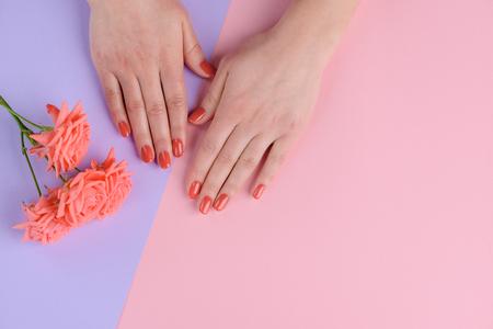 Korallenrosa Nägel und Blumen. Helle Farbe für eine romantische Person. Maniküresalonhintergrund mit Kopierraum.