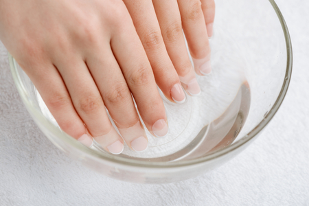 Warm bath for nails and dry skin. Mix of water and oil to soften cuticle. Proper care for hands.