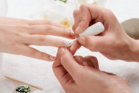 Manicurist painting on nails. Applying rhinestones and white polish lines. Simple and cute manicure.