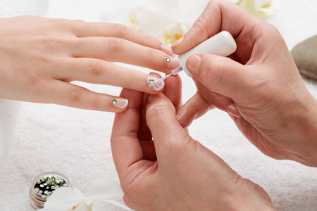 Specialist applying white nail polish with a brush. French manicure with rhinestones and stripe pattern. Stock Photo