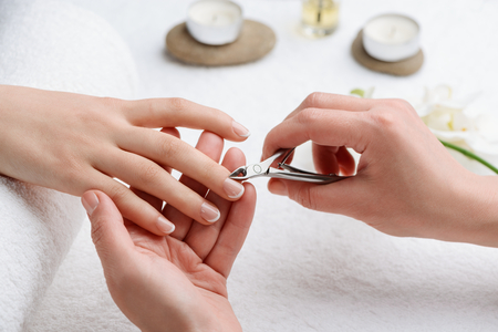 Careful removing of cuticle. Get rid of dead tissue for accurate and beautiful appearance of your nails. 免版税图像