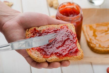 Gelee auf gesundem Brot verteilen